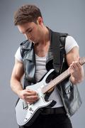 Handsome male rock musician is playing musical instrument - stock photo