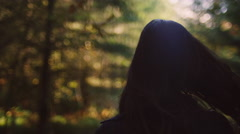 Beautiful girl in a forest walking away from the camera playing with her hair Stock Footage