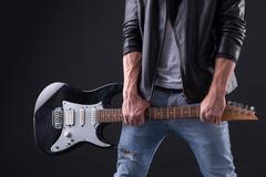 Skillful young rock musician with musical instrument - stock photo