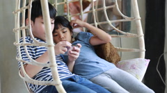 Little Asian boy and girl playing cell phone together in relax room Stock Footage