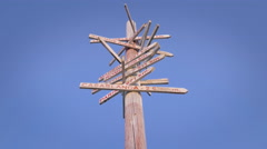 Vintage wooden signpost several city directions blue sky sunny day isolated tilt Stock Footage