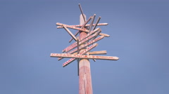 Old wooden signpost several city directions blue sky sunny day isolated tilt - stock footage