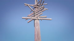 Old wooden traffic sign various city directions blue sky sunny day tilt Stock Footage