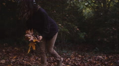 Beautiful girl in a forest picking autumn leaves up off the ground Stock Footage