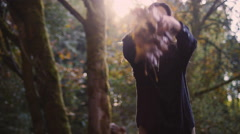 Beautiful girl in a forest throws leaves up in the air, bokeh Stock Footage