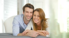 Portrait of cheerful couple laying on cushion Stock Footage
