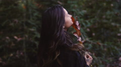 Beautiful girl in a forest holds a large leaf in front of her face Stock Footage