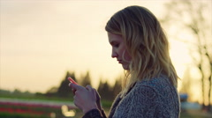 Young teen girl texting on phone outside in a field with a serious expression Stock Footage