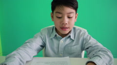 Happy Asian boy reading text with smile face on green backgroud - stock footage