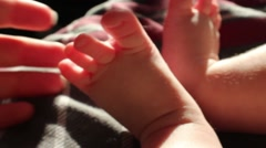 A mother's hand holding her baby's barefoot Stock Footage