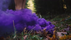 Beautiful girl in a dress spins around in purple smoke Stock Footage