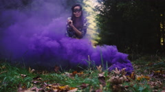 Beautiful girl in a mask plays around in purple smoke Stock Footage