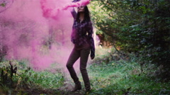Beautiful girl in a forest waves a pink smoke grenade around in circles Stock Footage