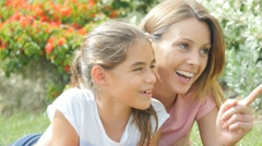 Mother and young girl relaxing in park - stock footage