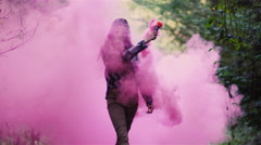 Beautiful girl in a forest spins around while holding a smoke grenade Stock Footage