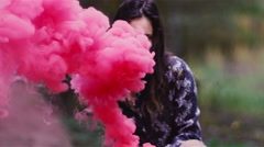 Beautiful girl in a forest waves around a color smoke grenade Stock Footage