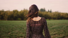 A beautiful girl in a dress with dark curly hair spinning and posing in a field - stock footage