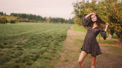 A beautiful girl in a dress with dark curly hair walking and posing in a field Stock Footage