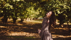 Beautiful girl in a dress spinning around and smiling in an orchard Stock Footage