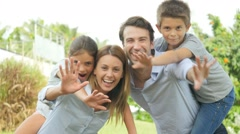 Cheerful family of four in garden Stock Footage