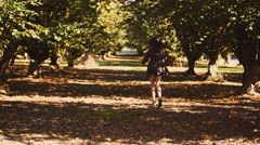 Beautiful girl in a dress running through trees in an orchard Stock Footage