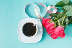 Cup of coffee and red roses on aquamarine background Stock Photos