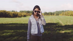 Beautiful girl wearing sunglasses in a field, slow motion Stock Footage