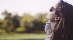 Beautiful girl wearing sunglasses in a field, close up Stock Footage