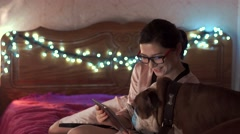 Pretty Asian girl and dog watching movie on her tablet Stock Footage