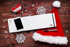 Christmas and New Year background with smartphone, red Santa's hat, notepad w Stock Photos