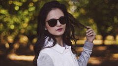 Beautiful girl with sunglasses in an orchard, in slow motion with bokeh Stock Footage