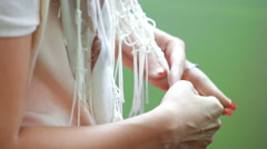 Female hands pulls the shawl fringe Stock Footage
