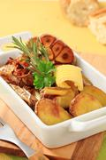 Dish of baked potatoes, garlic and onion Stock Photos