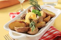 Halves of baked potatoes in a casserole dish - stock photo