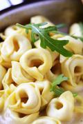 Tortellini and cream sauce in a saucepan - stock photo