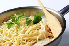 Spaghetti and creamy sauce in a saucepan Stock Photos