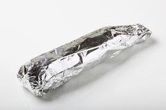 Raw pork tenderloin wrapped in aluminum foil - stock photo