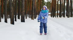 Girl running on snow-covered road. Steadicam video, slow motion video - stock footage