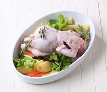 Raw chicken and vegetables in a casserole dish Stock Photos