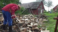 man chop hard big log near wood pile in country yard. 4K - stock footage