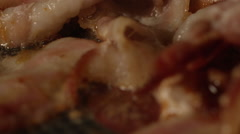 Macro shot of slow motion bacon frying in pan Stock Footage