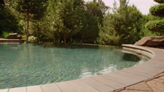 Beautiful outdoor pool with rippling water and green trees surrounding it Stock Footage