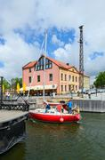 Yacht passes through moat of Dassel, Klaipeda, Lithuania Stock Photos