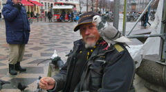 Homeless man feeding pigeons Stock Footage