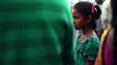 A young girl in green sells votive lamps Stock Footage