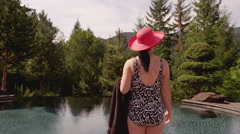 A young woman standing next to a pool looking out at the mountain view - stock footage
