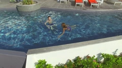 Couple swimming in infinity pool of luxury villa - stock footage