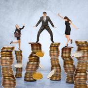 Business people standing on coins stack - stock photo