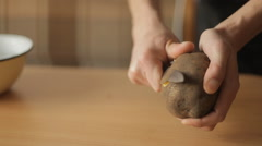 A man cleans the potatoes in the kitchen - stock footage