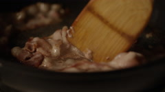 Slow motion bacon frying in pan - spatula stirring Stock Footage